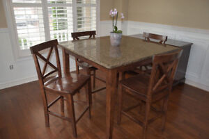 Counter height dining table with 4 chairs. Granite top.