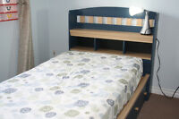 Mates twin bed with a head board and mattress.