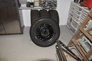 FOUR NEW WINTER TIRES (on new Cadillac steel rims)