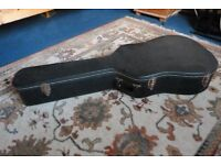 Acoustic guitar case. Wooden, covered in black faux leather. Slight rust on hinges, otherwise sound.
