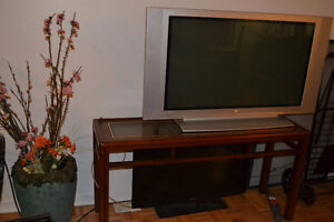 """Brown wooden frame glass top table with 42"""" plasma TV"""