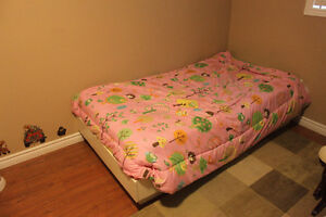 Twin bed with lots of bedding