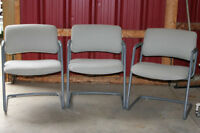Three grey office chairs