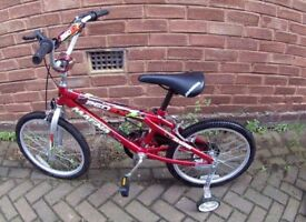 Boys red bike with stabilisers