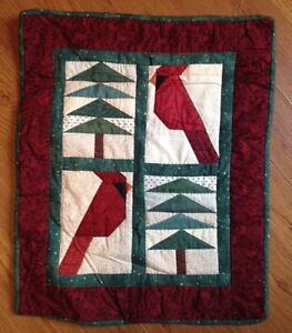 Quilted wall hanging with cardinals and pine trees