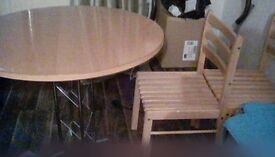 round table and four chairs and four brand new seat pads
