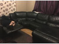 Black corner leather sofa with recliner, storage and cup holders