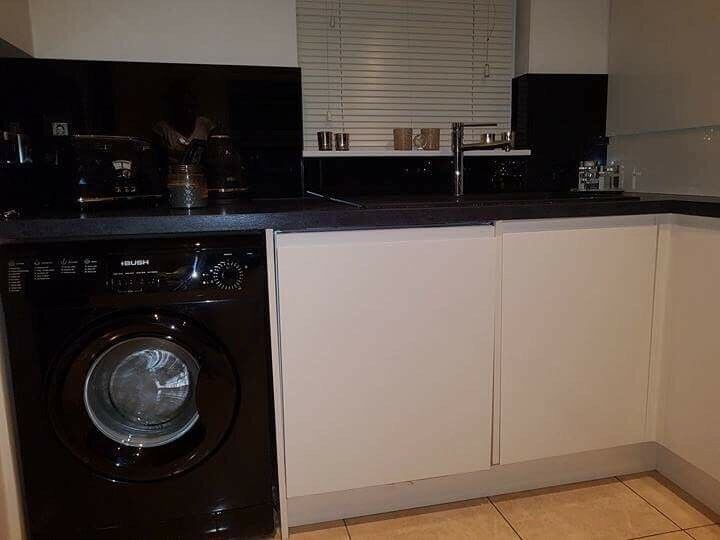 Cream gloss kitchen with 12 units, cooker and sink.