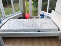 Single white IKEA bed with mattress