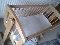 Swinging wooden crib with mattress, sheets and duvet