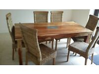 Solid hard wood dinning table . Six rattan rollback dinning chairs like new