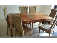 Solid hard wood dinning table . Two rattan rollback dinning chairs like new