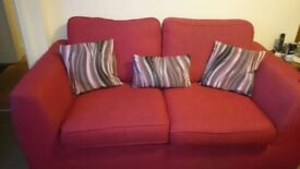 2 red sofas with cushions