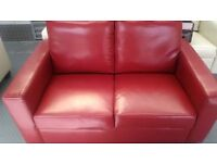 Red faux leather two seater sofa