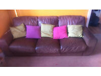 Comfy brown leather three seater sofa.
