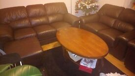 Beautiful brown leather couch, three, two, armchair and ottoman on legs