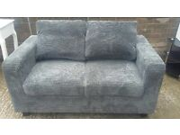 Almost new two seater grey sofa