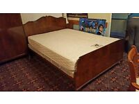 Wood and metal framed double bed with mattress and headboard.