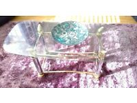 Glass coffee table and two matching side tables with silver/gold legs and struts.