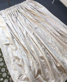 Pair of cream, pencil pleat, lined curtains with tie-backs.