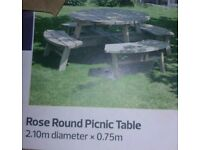 A brand new round chunky wooden picnic table x seats.