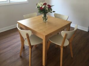IKEA wooden table with white chairs