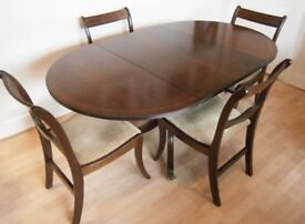 Antique drop-leaf mahogany dining table and four matching chairs.