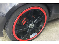 Ripspeed 17inch alloys in black laquer with a red rim edge, with a set of four part used tyres on.