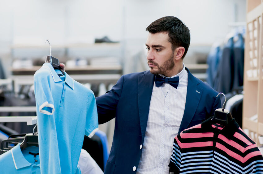 man inspecting two polo shirts