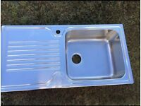 Stainless steel kitchen sink with mesh.