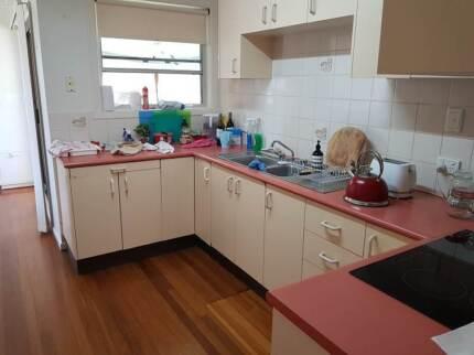 Kitchen cupboards, hotplate, oven, rangehood, sink.