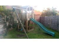 Kids outdoor wooden jungle gym playhouse. Swing, slide, table, climbing wall, net.