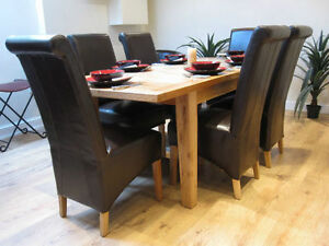 extending solid oak dining table and six black leather