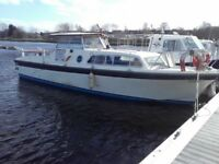 A Marine Project 31 Cabin Cruiser with Twin Volvo Engines, 4 Berths in 2 Cabins, Has a Rear Canopy.