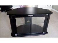 Curved black TV unit with glass doors and shelf