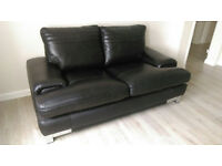 A comfy 2 seated sofa upholstered in attractive real dark dark brown colour leather