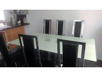 Glass table and 6 leather look and chrome chairs.