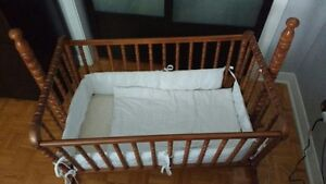 Antique wood bassinet with baby bumper and blanket