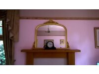 Large overmantle mirror. Gold wooden frame with top and side scrolls.