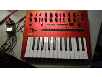 Korg Monologue boxed in red with mains adapter