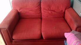 free red 2 seater sofa, sound but used so not spotless, collection only from bere alston pl20 7be