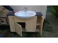 Ideal bathroom wash basin and toilet with granite effect vanity unit and lighting