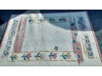 BEIGE/CREAMS PATTERNED TERRACOTTA BORDER RUG MEASURES APPROX 122 CM X 160 CM.