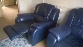 Two dark blue leather armchairs for sale, one recliner and one fixed, excellent condition.