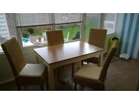 Extendable dining table and four chairs for sale.