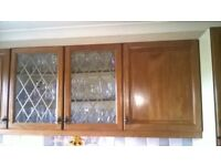 Dark Oak coloured wood, kitchen cupboard doors with handles and hinges.