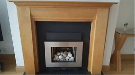 Wooden fire surround with slate composite back panel and hearth and gas fire