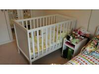 White cot with mattress and waterproof mattress protector.