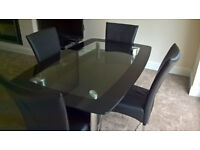 Glass dining table with four matching chairs