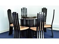 Circular, glass top dining table with six high back chairs and lazy susan